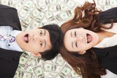 Förvånad affärsman och kvinna som ligger på pengarna Royaltyfri Foto