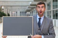 Förvånad affärsman som visar en svart tavla med utrymme för kopia Arkivbild