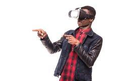 Förvånad afrikansk affärsman som använder oculusklyftahörlurar med mikrofon som erfar virtuell verklighet, medan spela videospele Arkivfoton