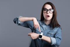 Förvånad bärande smartwatch för ung kvinna Fotografering för Bildbyråer