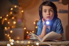Förvånad barnhåll i handficklampa royaltyfri fotografi