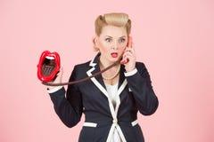 Förvånad blond krullningsflicka i blått omslag som talar vid den förvånade telefonen och bort ser med stora ögon över rosa bakgru arkivfoton