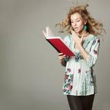 Förvånad blond kvinnaläsning en boka Royaltyfria Foton
