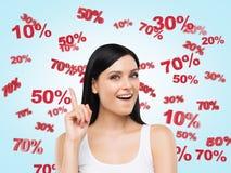 Förvånad brunett som omges av rabatt- och försäljningsnummer: 10% 20% 30% 50% 70% Royaltyfri Bild