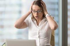 Förvånad chockad affärskvinna som ser bärbara datorn, huvud i händer royaltyfri bild