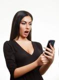 Förvånad chockad kvinna som ser telefonen Royaltyfri Foto