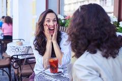 Förvånad dam som ser hennes vän och le Arkivbild