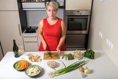 Förvånad flicka i bitande sparris för kök Royaltyfri Bild