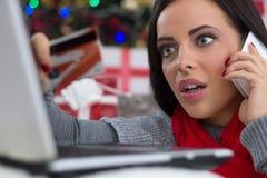 Förvånad flicka i en julnatt med mobiltelefonen och kreditering Arkivbilder