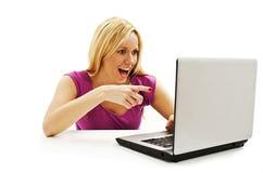 Förvånad flicka med bärbara datorn. Peka på den Arkivfoton