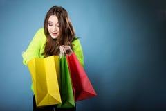Förvånad flicka med den pappers- shoppingpåsen. Försäljningar. Arkivbild