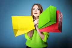 Förvånad flicka med den pappers- shoppingpåsen. Försäljningar. Arkivfoto