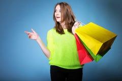 Förvånad flicka med den pappers- shoppingpåsen. Försäljningar. Royaltyfri Foto
