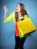 Förvånad flicka med den pappers- shoppingpåsen. Försäljningar. Arkivbilder