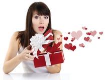 Förvånad flicka som öppnar en röd gåvaask Royaltyfri Foto