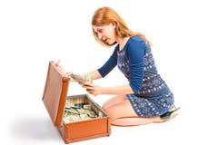Förvånad flicka som finnas i resväska av pengar Arkivbild