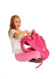 Förvånad flicka som pekar på ryggsäcken Arkivbild