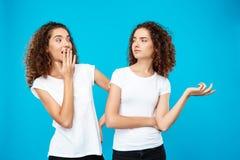 Förvånad flicka som ser hennes tvilling- over blåa bakgrund för syster Royaltyfri Foto