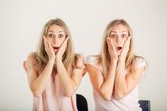 Förvånad flicka som ser hennes tvilling- over vita bakgrund för syster Fotografering för Bildbyråer
