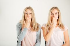 Förvånad flicka som ser hennes tvilling- over vita bakgrund för syster Arkivbild