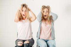 Förvånad flicka som ser hennes tvilling- over vita bakgrund för syster Arkivfoto