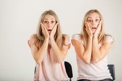 Förvånad flicka som ser hennes tvilling- over vita bakgrund för syster Royaltyfri Bild