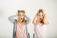 Förvånad flicka som ser hennes tvilling- over vita bakgrund för syster Royaltyfri Fotografi
