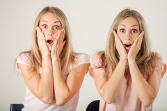 Förvånad flicka som ser hennes tvilling- over vita bakgrund för syster Arkivbilder