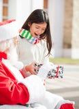 Förvånad flicka som tar gåvan från Santa Claus Royaltyfria Foton