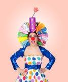 Förvånad flickaclown med en stor färgrik peruk Arkivbild