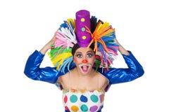 Förvånad flickaclown med en stor färgrik peruk royaltyfri fotografi