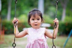 Förvånad framsida av den asiatiska gulliga lilla flickan medan henne som spelar gunga Royaltyfri Bild