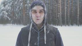Förvånad fryst man med exponeringsglas i snön som ser kameran i vinterskogen efter en snöstorm Royaltyfri Fotografi