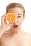 Förvånad härlig kvinna med en skiva av apelsinen Arkivfoton