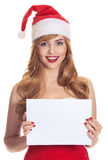 Förvånad julkvinna som slitage en santa hatt Arkivbilder