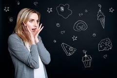 Förvånad känsla för ung kvinna, medan se priser i en supermarket royaltyfria bilder