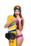 Förvånad kvinna i baddräkt som kramar snowboarden Arkivbild