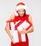 Förvånad kvinna i den santa hatten med många gåvaaskar Arkivbild