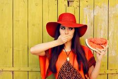 Förvånad kvinna i Red Hat med vattenmelonskivan Arkivbild