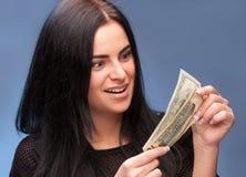 Förvånad kvinna med dollarräkningar Arkivfoto