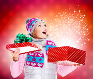 Förvånad kvinna med en julgåva med magiskt skina från b arkivbild
