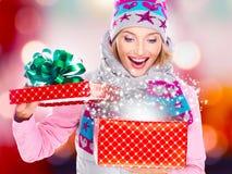 Förvånad kvinna med en julgåva med magiskt skina från b Royaltyfri Fotografi