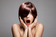 Förvånad kvinna med perfekt långt glansigt brunt hår royaltyfria foton