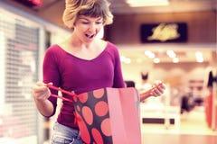 Förvånad kvinna som kontrollerar hennes shoppingpåsar och ler på modern royaltyfri foto