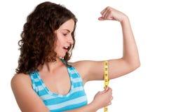 Förvånad kvinna som mäter henne Biceps Arkivbild