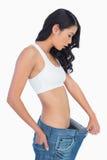 Förvånad kvinna som rymmer hennes för stora jeans Arkivbild