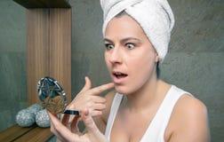 Förvånad kvinna som ser en aknefinne i spegel Arkivfoton