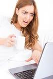 Förvånad kvinna som ser i skärmen av bärbara datorn som får dålig informat Arkivbild