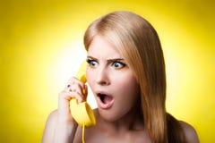 Förvånad kvinna som talar på den gula telefonen Arkivfoton