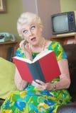 Förvånad kvinnaläsebok Royaltyfri Foto